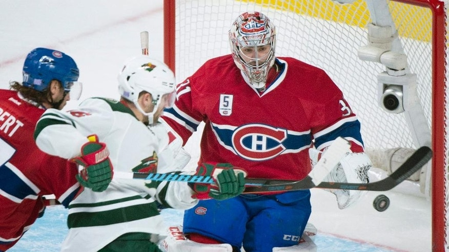 Montreal Canadiens goaltender Carey Price makes a save against Minnesota Wild's Jason Zucker, center, as Canadiens' Tom Gilbert defends during the third period of an NHL hockey game Saturday, Nov. 8, 2014, in Montreal. (AP Photo/The Canadian Press, Graham Hughes)