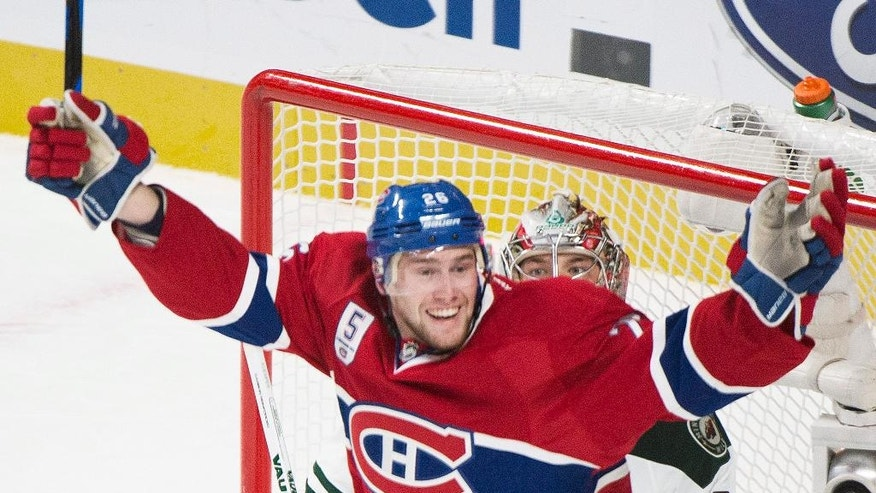 Montreal Canadiens' Jiri Sekac celebrates a goal by teammate Lars Eller as Minnesota Wild goaltender Darcy Kuemper watches during the second period of an NHL hockey game Saturday, Nov. 8, 2014, in Montreal. (AP Photo/The Canadian Press, Graham Hughes)