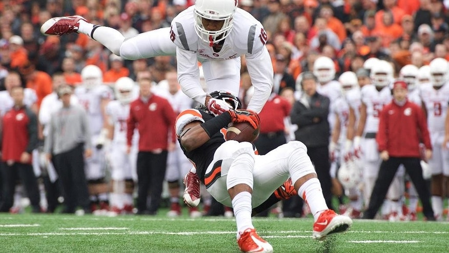 Washington State defender Charleston White (16) tackles Oregon State receiver Jordan Villain (13) during an NCAA college football game in Corvallis, Ore., Saturday, Nov. 8, 2014. (AP Photo/Troy Wayrynen)