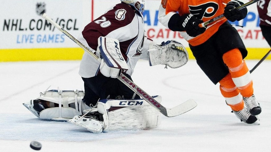 Philadelphia Flyers' Brayden Schenn (10), right, chases the loose puck around Colorado Avalanche goalie Reto Berra (20), left, during the second period of their NHL hockey game, Saturday, Nov. 8, 2014, in Philadelphia. (AP Photo/Tom Mihalek)