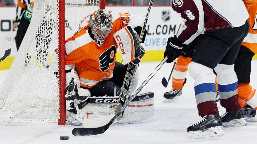 Philadelphia Flyers goalie Steve Mason (35), left, defends as Colorado Avalanche' Jan Hejda (8), right, tries to score in the first period of an NHL hockey game, Saturday, Nov. 8, 2014, in Philadelphia. (AP Photo/Tom Mihalek)