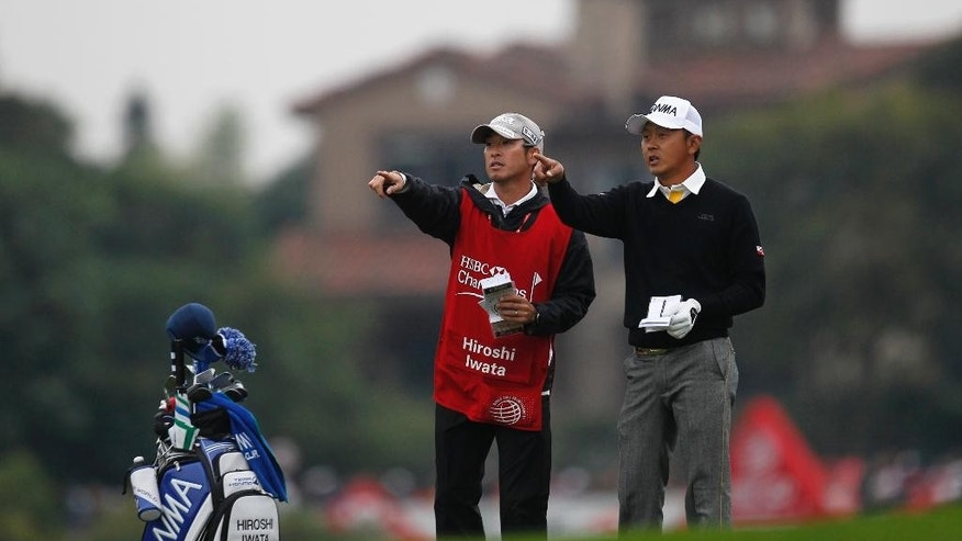 Hiroshi Iwata of Japan, right, points forward with his caddie on the 18th hole during the 3rd round of the HSBC Champions golf tournament at the Sheshan International Golf Club in Shanghai, China, Saturday, Nov. 8, 2014. (AP Photo)