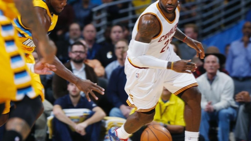 Denver Nuggets forward Kenneth Faried, left, pursues a loose ball with Cleveland Cavaliers forward LeBron James in the first quarter of an NBA basketball game in Denver on Friday, Nov. 7, 2014. (AP Photo/David Zalubowski)