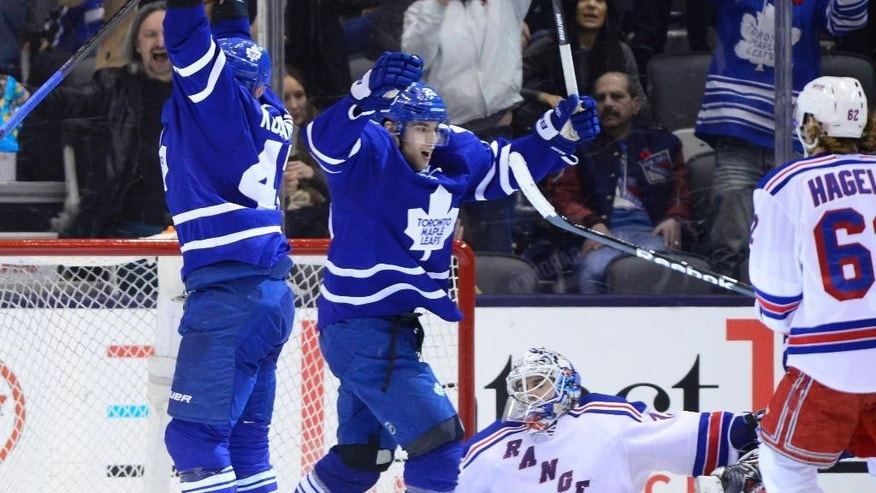 Toronto Maple Leafs' Leo Komarov, left, celebrates his goal with teammate Mike Santorelli as New York Rangers goaltender Cam Talbot and Rangers' Carl Hagelin watch during the third period of an NHL hockey game Saturday, Nov. 8, 2014, in Toronto. (AP Photo/The Canadian Press, Fred Gunn)