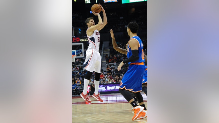 Atlanta Hawks guard Kyle Korver (26) shoots in front of New York Knicks guard Shane Larkin during the first half of an NBA basketball game, Saturday, Nov. 8, 2014, in Atlanta. Atlanta won 103-96 with Korver leading all scorers with 27 points. (AP Photo/John Amis)