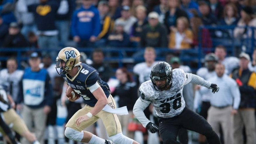 In this photo provided by Montana State University, Portland State linebacker Jeremy Lutali (30) chases Montana State quarterback Dakota Prukop (5) during the first half of an NCAA football game Saturday, Nov. 8,  2014 in Bozeman, Mont. (AP Photo/Montana State University, Kelly Gorham)