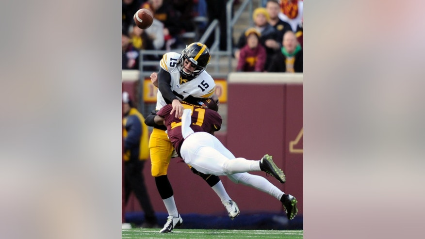 Iowa quarterback Jake Rudock (15) throws a pass as he is hit by Minnesota defensive back Eric Murray (31) during the first half of an NCAA college football game on Saturday, Nov. 8, 2014, in Minneapolis. (AP Photo/Hannah Foslien)
