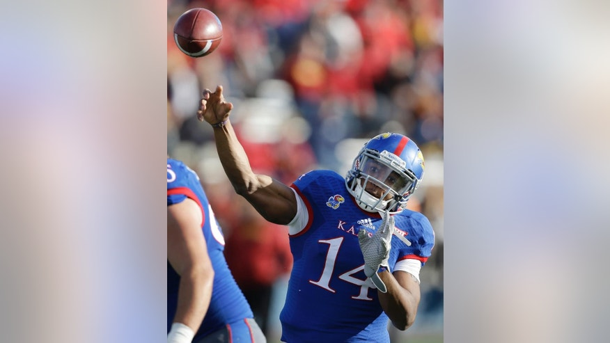 Kansas quarterback Michael Cummings (14) passes to a teammate during the first half of an NCAA college football game against Iowa State in Lawrence, Kan., Saturday, Nov. 8, 2014. (AP Photo/Orlin Wagner)