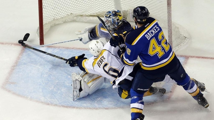 Nashville Predators' Shea Weber (6) reaches for a puck as St. Louis Blues goalie Brian Elliott and David Backes (42) defend during the second period of an NHL hockey game, Saturday, Nov. 8, 2014, in St. Louis. (AP Photo/Jeff Roberson)