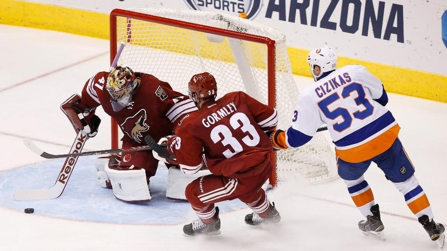 Arizona Coyotes' Mike Smith (41) makes a save on a shot by New York Islanders' Casey Cizikas (53) as Coyotes' Brandon Gormley (33) defends during the second period of an NHL hockey game Saturday, Nov. 8, 2014, in Glendale, Ariz. (AP Photo/Ross D. Franklin)