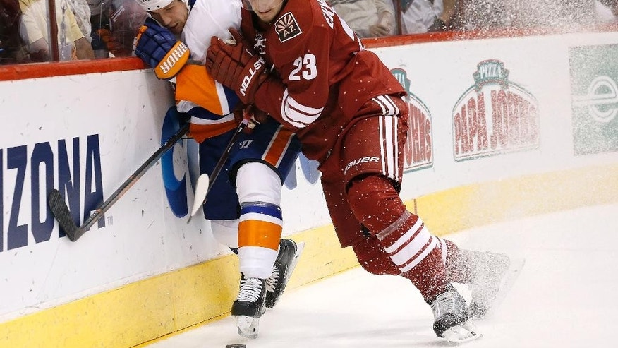 Arizona Coyotes' Oliver Ekman-Larsson (23), of Sweden, checks New York Islanders' Casey Cizikas (53) into the boards during the first period of an NHL hockey game Saturday, Nov. 8, 2014, in Glendale, Ariz. (AP Photo/Ross D. Franklin)