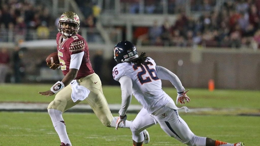 Florida State's Jameis Winston, left, evades Virginia's Maurice Canady to pick up yardage in the first quarter of an NCAA college football game, Saturday, Nov. 8, 2014, in Tallahassee, Fla. (AP Photo/Steve Cannon)