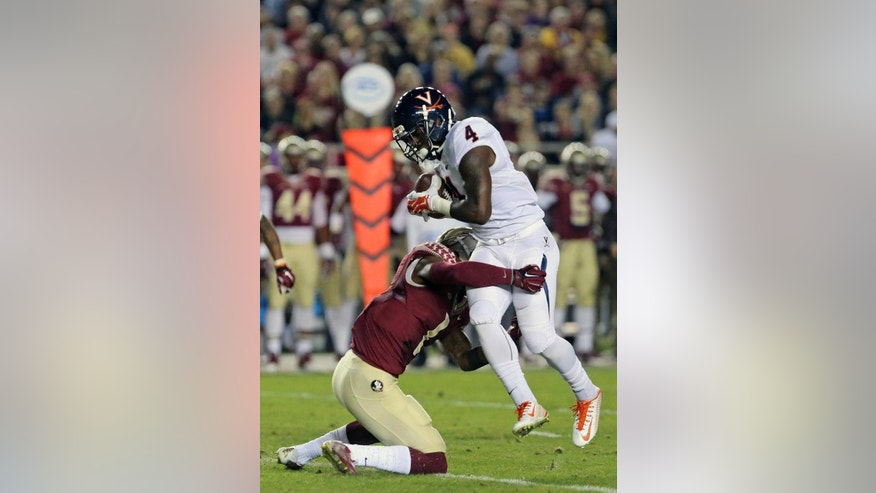 Florida State's Tyler Hunter, left, tackles Virginia's Taquan Mizzell (4) in the first quarter of an NCAA college football game, Saturday, Nov. 8, 2014, in Tallahassee, Fla. (AP Photo/Steve Cannon)