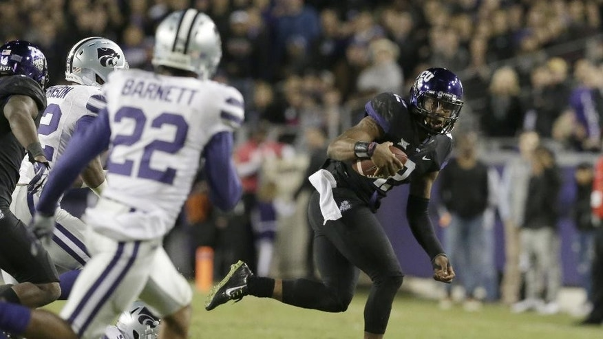 TCU quarterback Trevone Boykin (2) runs against Kansas State defensive back Dante Barnett (22) and linebacker Elijah Lee (9) during the second quarter of an NCAA college football game Saturday, Nov. 8, 2014, in Fort Worth, Texas. (AP Photo/LM Otero)