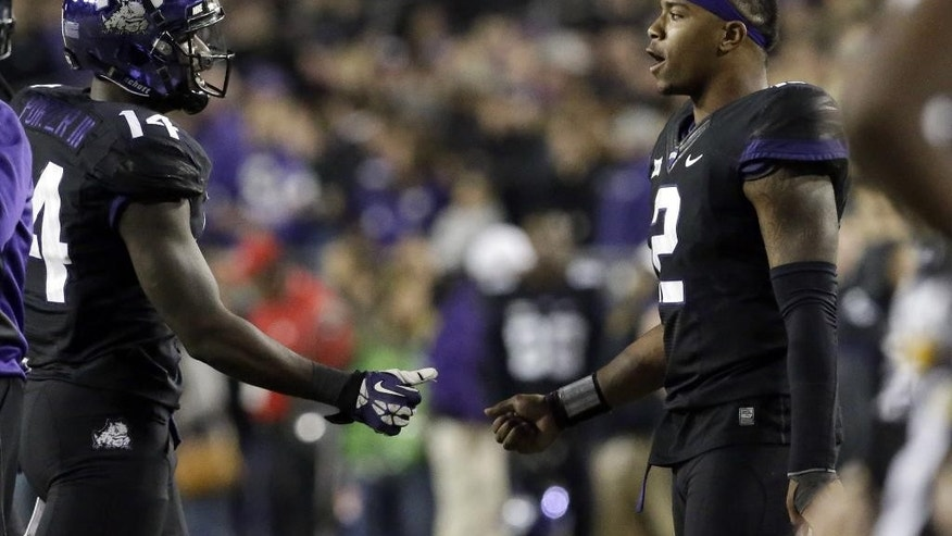 TCU quarterback Trevone Boykin (2) and wide receiver David Porter (14) greet each other during a timeout during the second quarter of an NCAA college football game against Kansas State, Saturday, Nov. 8, 2014, in Fort Worth, Texas. (AP Photo/LM Otero)