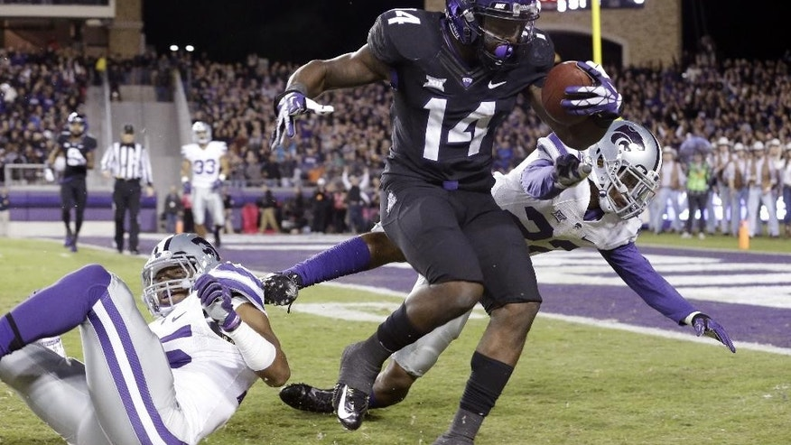 TCU wide receiver David Porter (14) makes a catch against Kansas State defensive backs Dante Barnett (22) and Randall Evans (15) during the first quarter of an NCAA college football game  Saturday, Nov. 8, 2014, in Fort Worth, Texas.  (AP Photo/LM Otero)