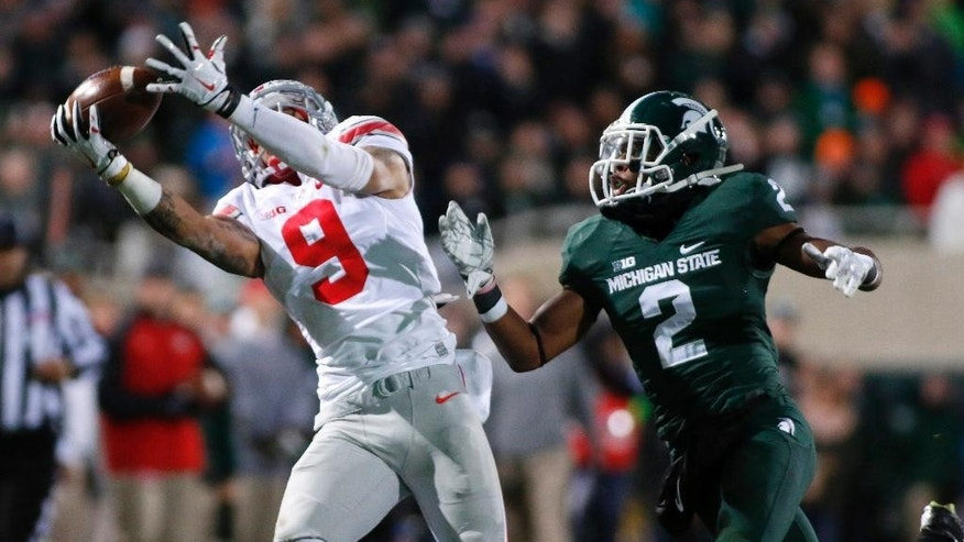 Ohio State receiver Devin Smith (9) pulls in a 43-yard pass against Michigan State's Darian Hicks (2) during the second quarter of an NCAA college football game, Saturday, Nov. 8, 2014, in East Lansing, Mich. (AP Photo/Al Goldis)