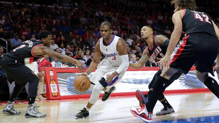Los Angeles Clippers' Chris Paul, center, drives past Portland Trail Blazers' Wesley Matthews, left, and Damian Lillard as Trail Blazers' Robin Lopez, right, watches during the first half of an NBA basketball game Saturday, Nov. 8, 2014, in Los Angeles. (AP Photo/Jae C. Hong)