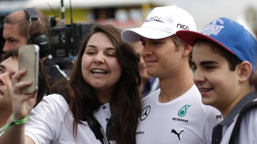 Mercedes driver Nico Rosberg, of Germany, poses for a selfie with fans upon his arrival to the the Interlagos race track in Sao Paulo, Brazil, Saturday, Nov. 8, 2014.The Formula 1 Brazilian Grand Prix will take place Nov. 9. (AP Photo/Felipe Dana)