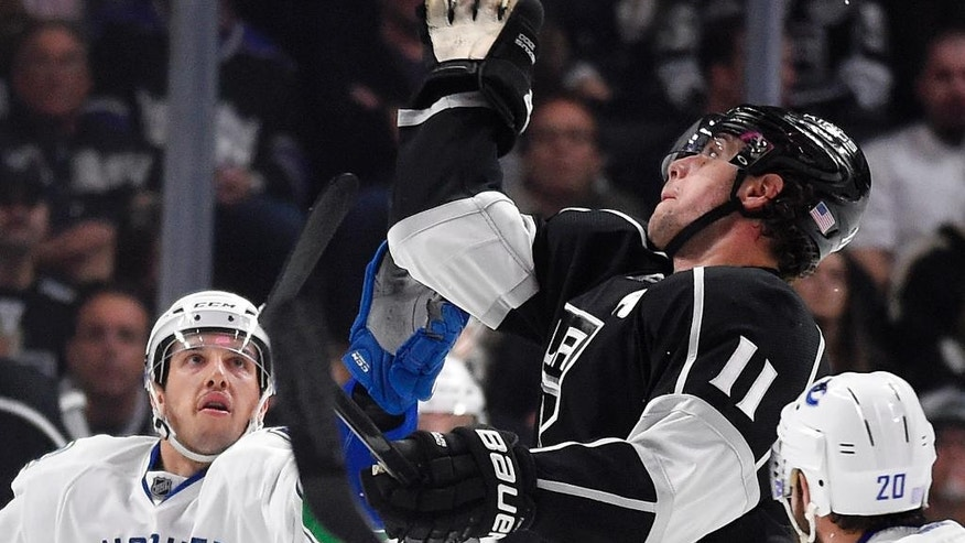 Los Angeles Kings center Anze Kopitar, center, of Slovenia, grabs a puck as Vancouver Canucks center Nick Bonino, left, and left wing Chris Higgins watch during the second period of an NHL hockey game, Saturday, Nov. 8, 2014, in Los Angeles. (AP Photo/Mark J. Terrill)