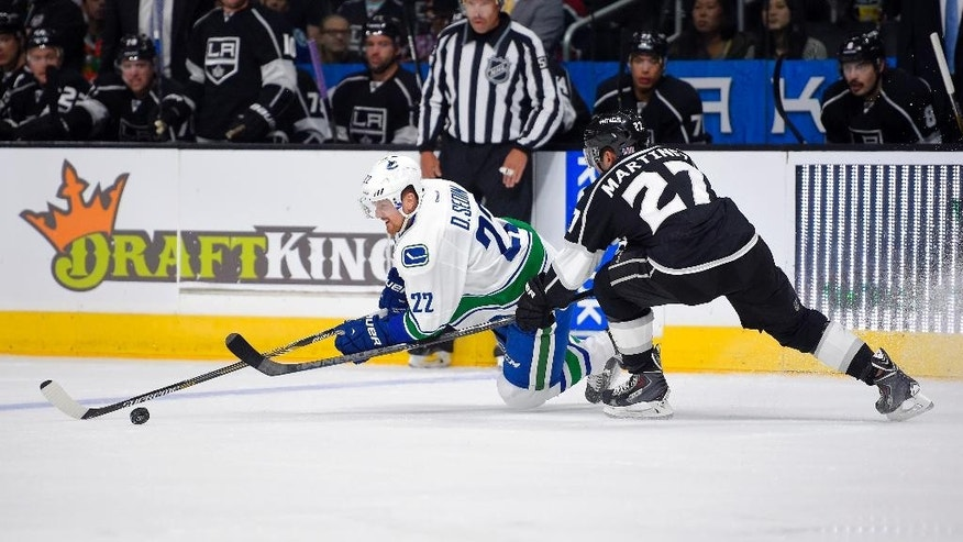 Vancouver Canucks left wing Daniel Sedin, left, of Sweden, and Los Angeles Kings defenseman Alec Martinez vie for the puck during the first period of an NHL hockey game, Saturday, Nov. 8, 2014, in Los Angeles. (AP Photo/Mark J. Terrill)
