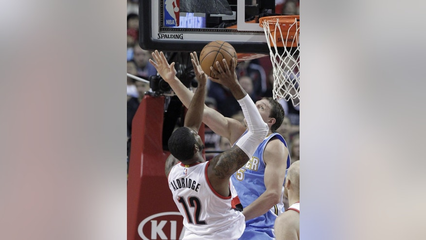 Portland Trail Blazers forward LaMarcus Aldridge, left, shoots against Denver Nuggets center Timofey Mozgov, from Russia,  during the first half of an NBA basketball game in Portland, Ore., Sunday, Nov. 9, 2014. (AP Photo/Don Ryan)