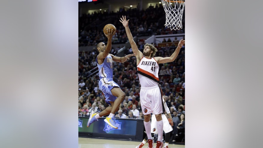 Denver Nuggets guard Arron Afflalo, left, drives to the hoop against Portland Trail Blazers center Robin Lopez during the first half of an NBA basketball game in Portland, Ore., Sunday, Nov. 9, 2014. (AP Photo/Don Ryan)
