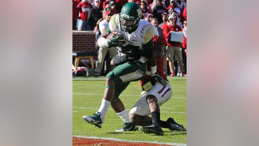 Baylor running back Shock Linwood (32) runs into the end zone for a touchdown ahead of Oklahoma safety Quentin Hayes, right, in the fourth quarter of an NCAA college football game in Norman, Okla., Saturday, Nov. 8, 2014. Baylor won 48-14. (AP Photo/Sue Ogrocki)
