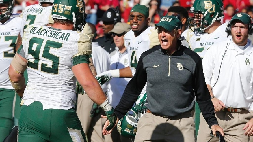 Baylor head coach Art Briles celebrates on the sidelines following a sack of Oklahoma quarterback Trevor Knight in the fourth quarter of an NCAA college football game in Norman, Okla., Saturday, Nov. 8, 2014. Baylor won 48-14. (AP Photo/Sue Ogrocki)