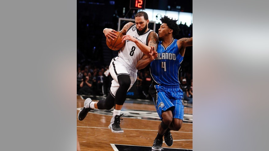 Brooklyn Nets' Deron Williams (8) drives against Orlando Magic's Elfrid Payton (4) during the fourth quarter of an NBA basketball game Sunday, Nov. 9, 2014, in New York. Brooklyn won 104-96. (AP Photo/Jason DeCrow)