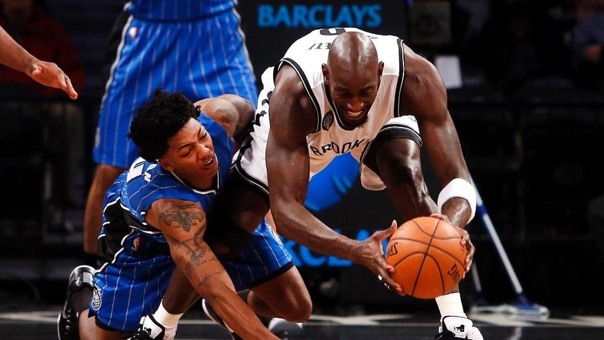 Brooklyn Nets' Kevin Garnett, right, grabs a loose ball away from Orlando Magic's Elfrid Payton during the first quarter of an NBA basketball game Sunday, Nov. 9, 2014, in New York. (AP Photo/Jason DeCrow)