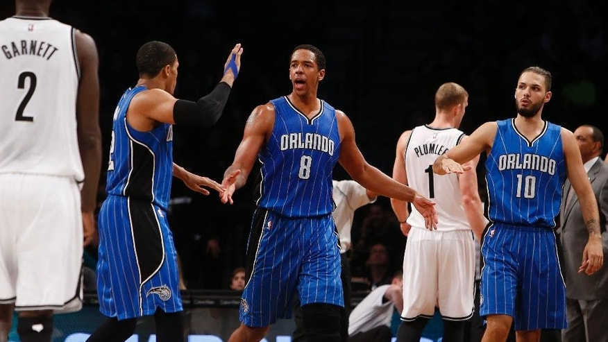 Orlando Magic's Channing Frye (8) celebrates with teammates Tobias Harris, left, and Evan Fournier (10), of France, after scoring a 3-point basket against the Brooklyn Nets during the second quarter of an NBA basketball game Sunday, Nov. 9, 2014, in New York. (AP Photo/Jason DeCrow)