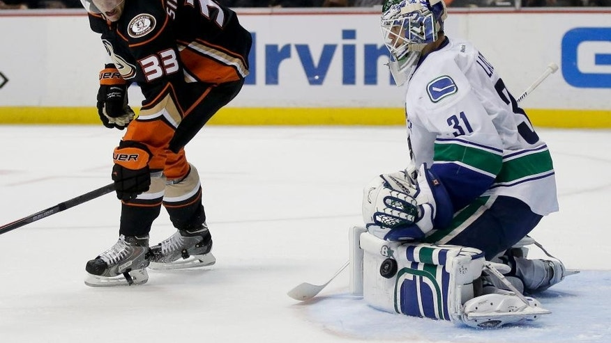 Vancouver Canucks goalie Eddie Lack blocks a shot as Anaheim Ducks right wing Jakob Silfverberg watches during the second period of an NHL hockey game in Anaheim, Calif., Sunday, Nov. 9, 2014. (AP Photo/Chris Carlson)