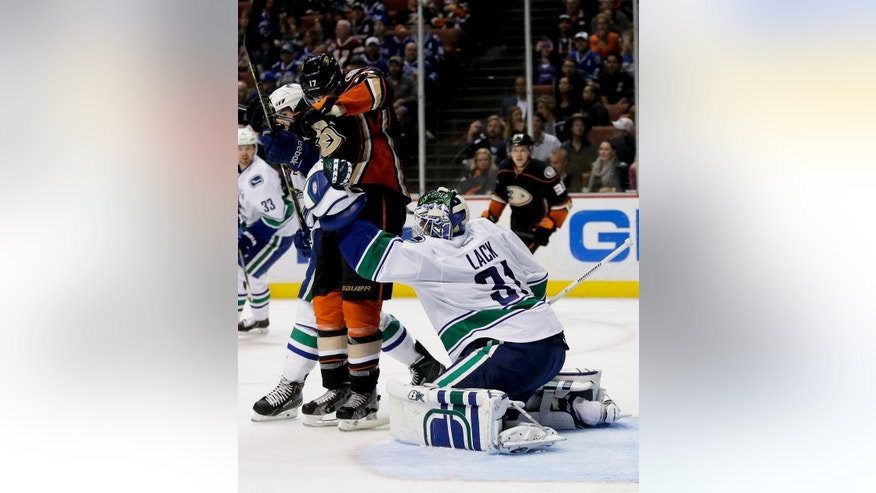 Vancouver Canucks goalie Eddie Lack blocks a shot as Anaheim Ducks center Ryan Kesler watches during the second period of an NHL hockey game in Anaheim, Calif., Sunday, Nov. 9, 2014. (AP Photo/Chris Carlson)