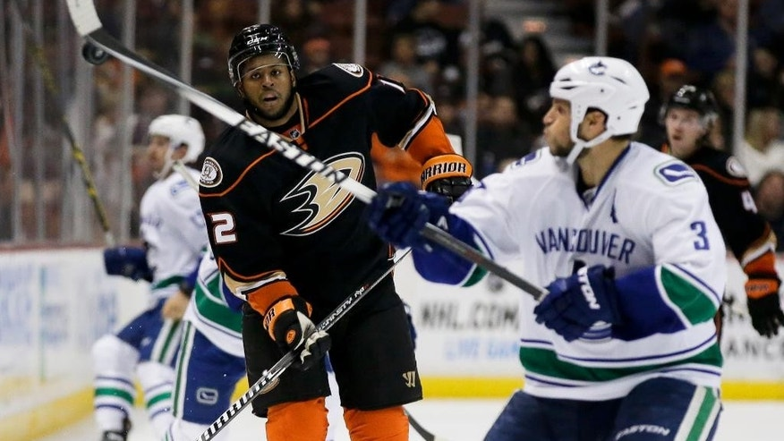Vancouver Canucks defenseman Kevin Bieksa, right, blocks a pass as Anaheim Ducks right wing Devante Smith-Pelly watches during the second period of an NHL hockey game in Anaheim, Calif., Sunday, Nov. 9, 2014. (AP Photo/Chris Carlson)