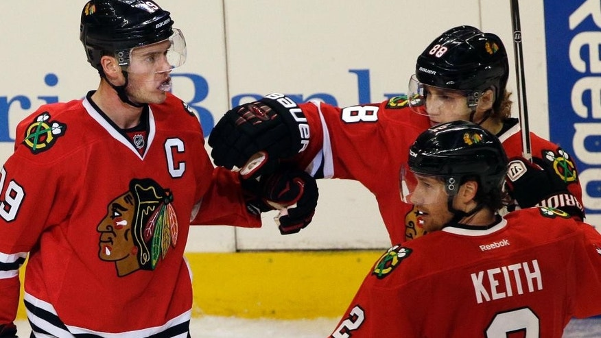 Chicago Blackhawks center Jonathan Toews (19) celebrates with right wing Patrick Kane (88) and defenseman Duncan Keith (2) after scoring against the San Jose Sharks during the third period of an NHL hockey game in Chicago, Sunday, Nov. 9, 2014. The Blackhawks won 5-2. (AP Photo/Nam Y. Huh)