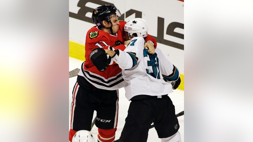Chicago Blackhawks right wing Jeremy Morin (11) fights with San Jose Sharks right wing Adam Burish (37) during the third period of an NHL hockey game in Chicago, Sunday, Nov. 9, 2014. The Blackhawks won 5-2. (AP Photo/Nam Y. Huh)