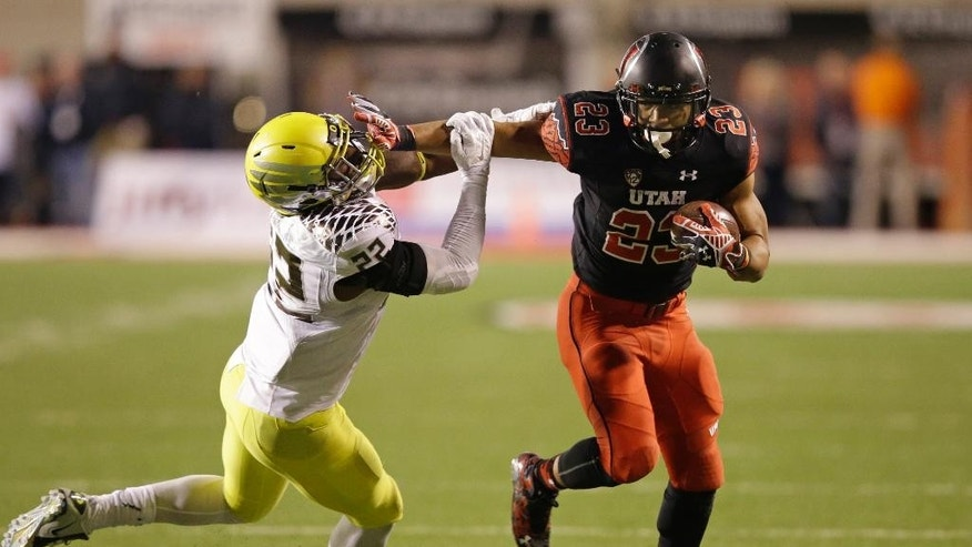 Oregon linebacker Derrick Malone (22) attempts to make a tackle as Utah running back Devontae Booker (23) carries the ball in the second quarter during an NCAA college football game Saturday, Nov. 8, 2014, in Salt Lake City. (AP Photo/Rick Bowmer)