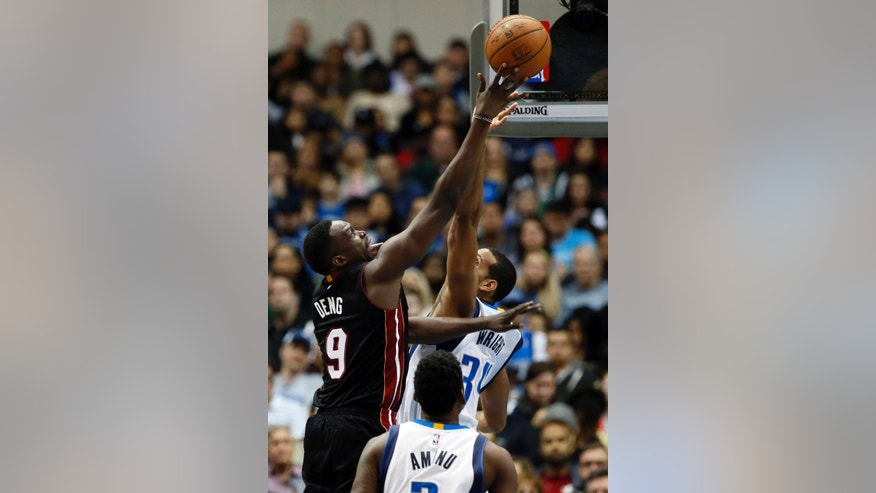 Miami Heat's Luol Deng (9) shoots over Dallas Mavericks' Brandan Wright (34) as Al-Farouq Aminu, front, watches during the second half of an NBA basketball game, Sunday, Nov. 9, 2014, in Dallas. Deng led all scoring with 30 points in the 105-96 Heat win. (AP Photo/Tony Gutierrez)