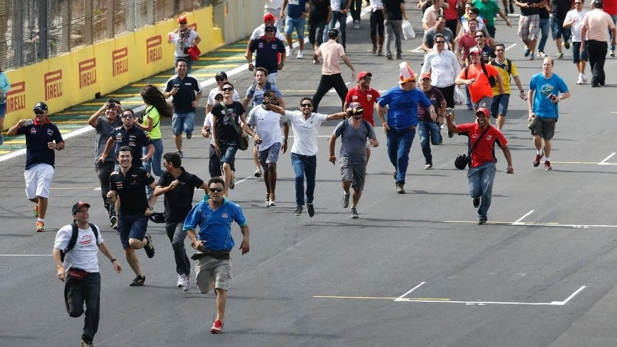Fans invade the track to celebrate the third place finish of Williams driver Felipe Massa, of Brazil, at the end of the Formula One Brazilian Grand Prix at the Interlagos race track in Sao Paulo, Brazil, Sunday, Nov. 9, 2014. (AP Photo/Andre Penner)