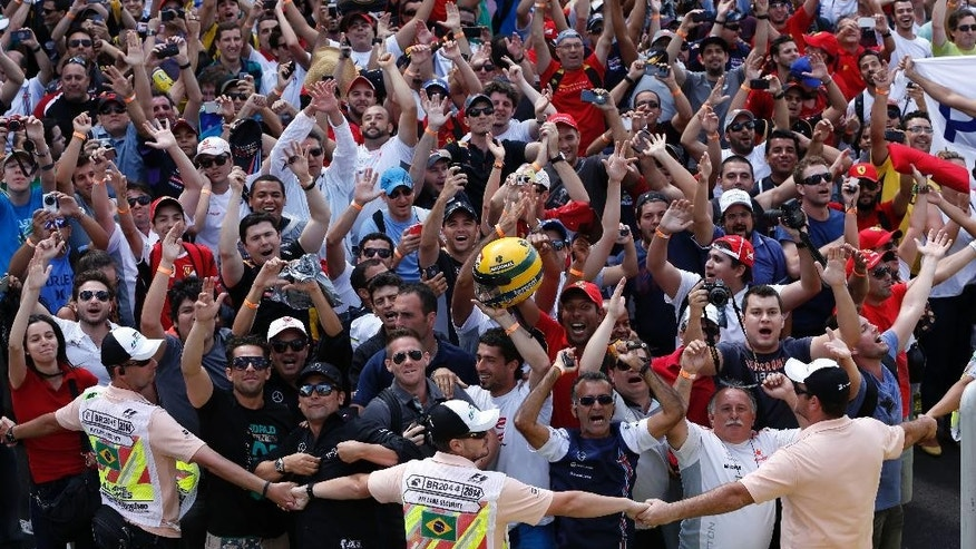 Security guards hold back fans that invaded the track to celebrate the third place of Williams driver Felipe Massa, of Brazil, at the end of the Formula One Brazilian Grand Prix at the Interlagos race track in Sao Paulo, Brazil, Sunday, Nov. 9, 2014. Mercedes driver Nico Rosberg of Germany fended off a strong charge by Lewis Hamilton to win the Brazilian Grand Prix on Sunday, closing in on his Mercedes teammate in the Formula One title race. (AP Photo/Andre Penner)