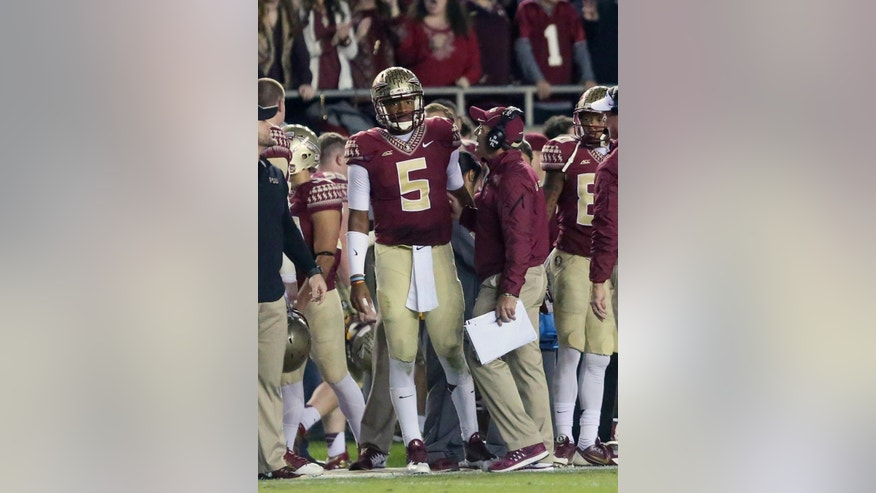 Florida State's head coach Jimbo Fisher, right, talks with quarterback Jameis Winston (5) on the sideline as the play against Virginia in the second quarter of an NCAA college football game, Saturday, Nov. 8, 2014, in Tallahassee, Fla. Florida State won the game 34-20. (AP Photo/Steve Cannon)