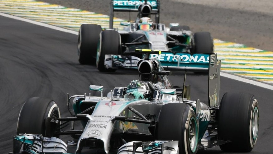 Mercedes driver Nico Rosberg of Germany, leads the race followed by teammate Lewis Hamilton of Britain, during the Formula One Brazilian Grand Prix at the Interlagos race track in Sao Paulo, Brazil, Sunday, Nov. 9, 2014. Rosberg fended off a strong charge by Lewis Hamilton to win the Brazilian Grand Prix on Sunday, closing in on his Mercedes teammate in the Formula One title race. (AP Photo/Andre Penner)