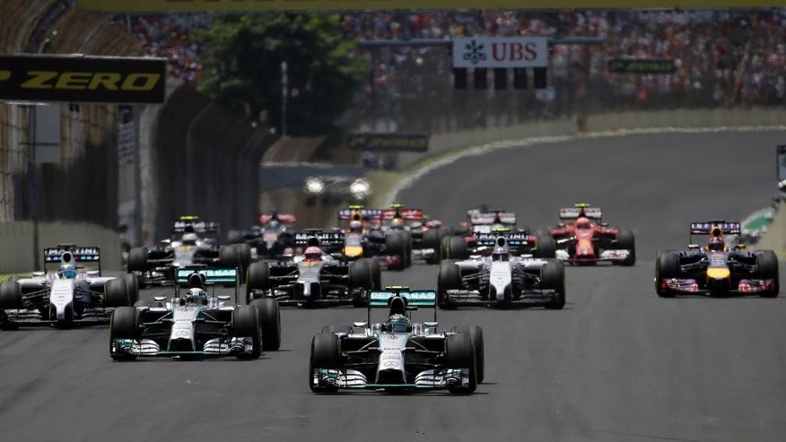 Mercedes driver Nico Rosberg , center, of Germany leads the field away from the starting grid the Formula One Brazilian Grand Prix at the Interlagos race track in Sao Paulo, Brazil, Sunday, Nov. 9, 2014. Rosberg of Germany, fended off a strong charge by Lewis Hamilton to win the Brazilian Grand Prix on Sunday, closing in on his Mercedes teammate in the Formula One title race. (AP Photo/Felipe Dana)