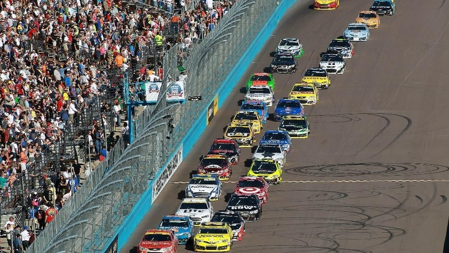 Drivers Kevin Harvick , front left, and Matt Kenseth lead the field on a green flag re-start during the Quicken Loans Race for Heroes 500 NASCAR Sprint Cup Series auto race at Phoenix International Raceway, Sunday, Nov. 9, 2014, in Avondale, Ariz. (AP Photo/Ralph Freso)