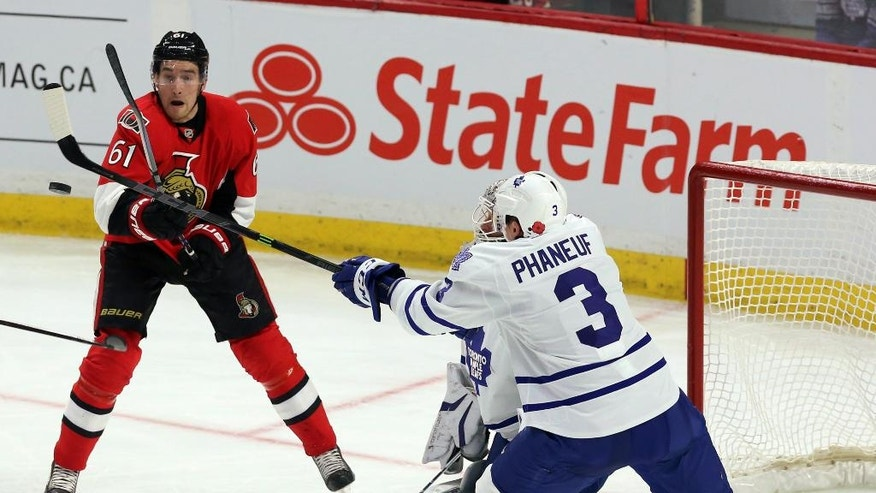 Toronto Maple Leafs' Dion Phaneuf (3) and Ottawa Senators Mike Stone (61) bat at a flying puck during the second period of an NHL hockey game in Ottawa, Ontario, Sunday, Nov. 9, 2014. (AP Photo/The Canadian Press, Fred Chartrand)