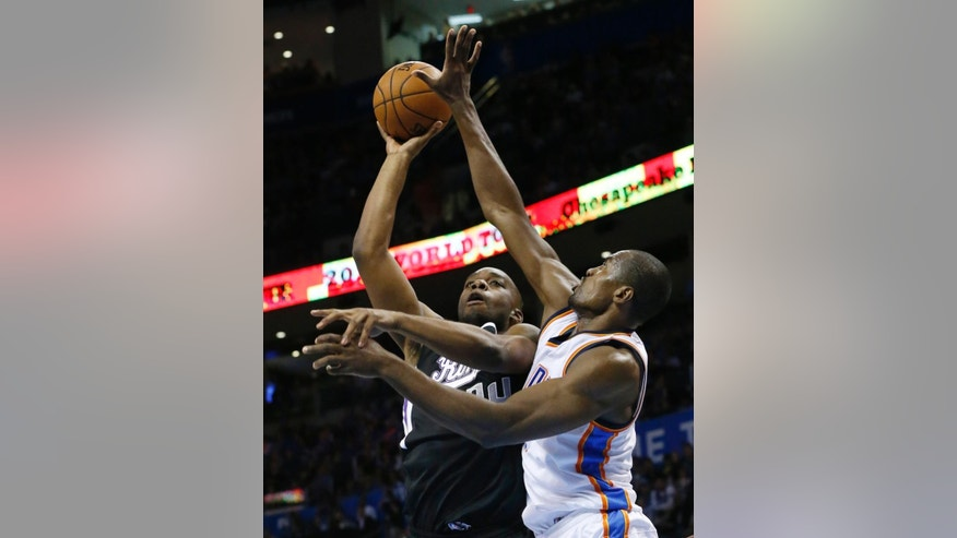 Oklahoma City Thunder forward Serge Ibaka (9) defends as Sacramento Kings forward Carl Landry (24) shoots in the first quarter of an NBA basketball game in Oklahoma City, Sunday, Nov. 9, 2014. (AP Photo/Sue Ogrocki)