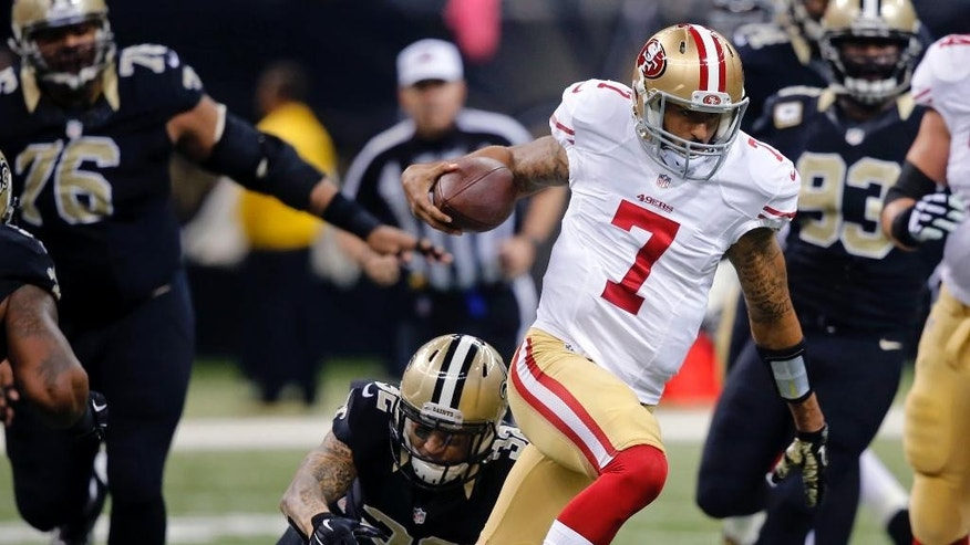 San Francisco 49ers quarterback Colin Kaepernick (7) carries past New Orleans Saints strong safety Kenny Vaccaro (32) in the first half of an NFL football game in New Orleans, Sunday, Nov. 9, 2014. (AP Photo/Bill Haber)
