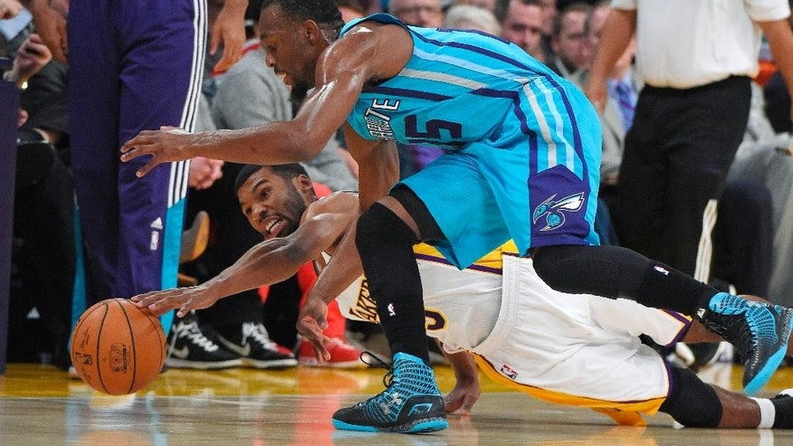 Los Angeles Lakers guard Ronnie Price, below, and Charlotte Hornets guard Kemba Walker go after a loose ball during the first half of an NBA basketball game, Sunday, Nov. 9, 2014, in Los Angeles. (AP Photo/Mark J. Terrill)