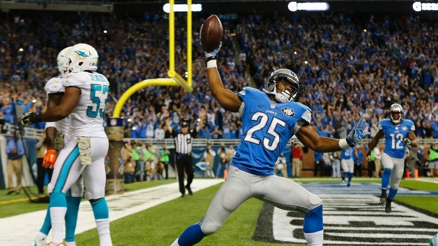 Detroit Lions running back Theo Riddick (25) celebrates a touchdown during the second half of an NFL football game against the Miami Dolphins in Detroit, Sunday, Nov. 9, 2014. (AP Photo/Paul Sancya)